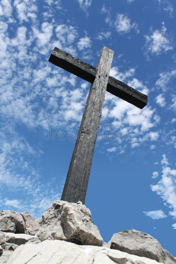 Cross in barren setting. A cross stands on a foundation of rocks royalty free stock photo