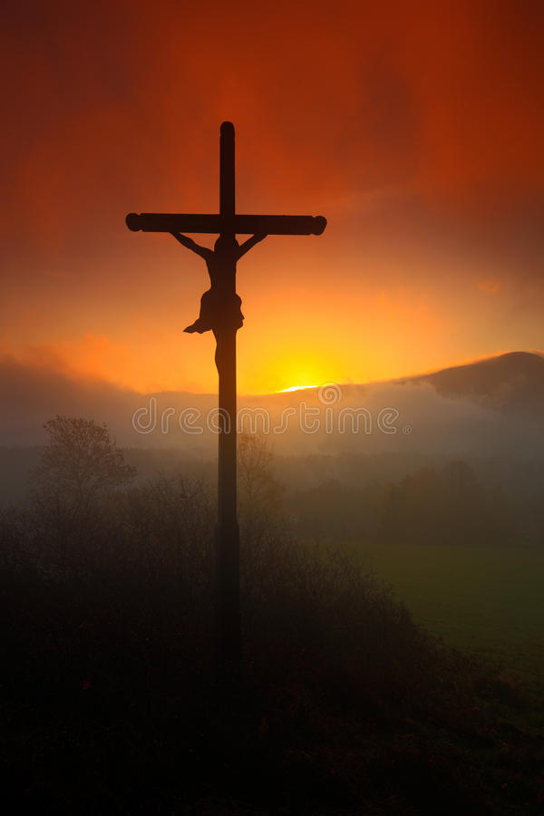 Cross with beautiful sunset with fog. Czech landscape with cross with orange sun and clouds during morning. Hilly mystic landscape stock photos