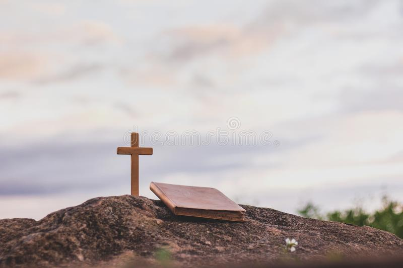 The cross and the bible is on the rock, sins and prayer. royalty free stock photography