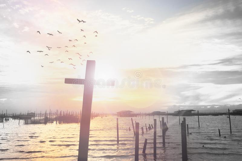 Cross on blurry sunset background. Religious cross against the background of the rays of the setting sun, symbolizing `faith`. Abstract religious composition stock photo
