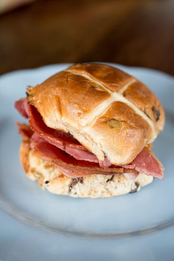 Cross Bun on a White Round Plate. Bacon cross bun on a white round plate royalty free stock image