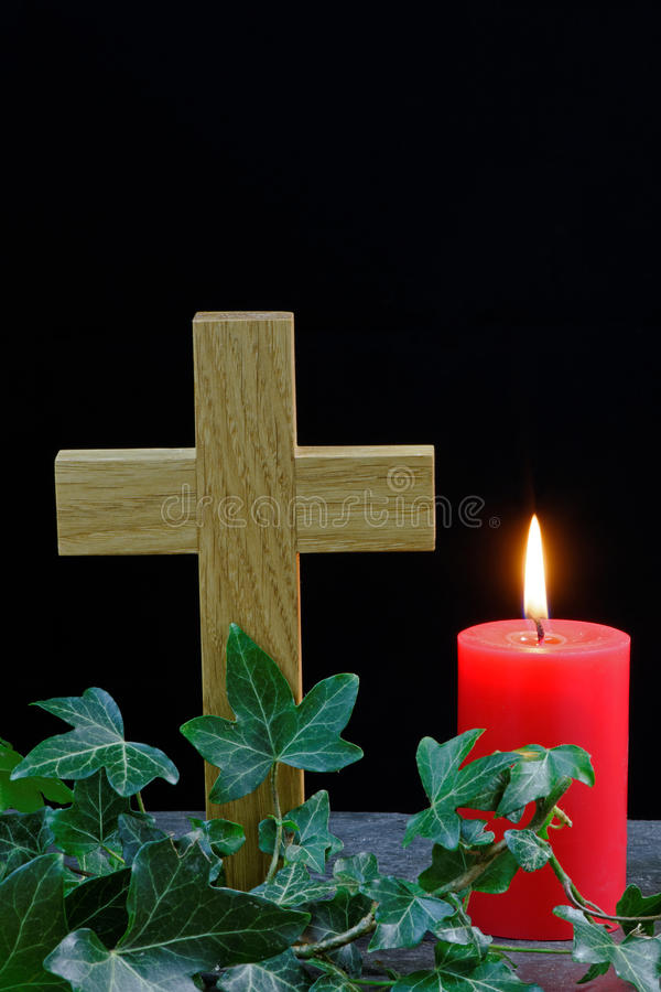 Cross and Candle. Candle and cross on slate with ivy. Holy symbols for Christian celebrations stock photos