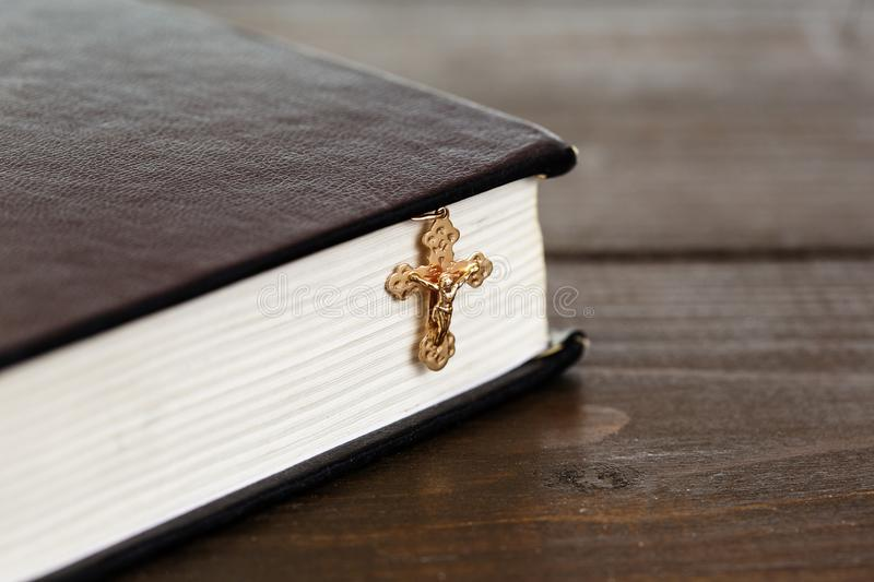 A cross with a chain next to a closed book. Christian gold cross with a chain near a closed Holy Bible on wooden surface. The Way to God through Prayer and Faith royalty free stock images