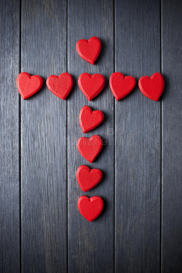Cross Christian Religion Love. A cross made of red love hearts on a wood background stock photo