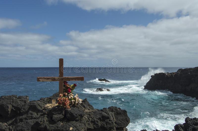 Cross on clifftop and with crashing waves below stock photography