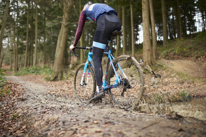 Cross-country cyclist riding in mud, low angle back view stock photo