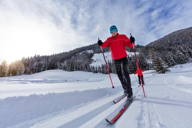 Cross-country skiing. Young man and woman doing exercise stock photos