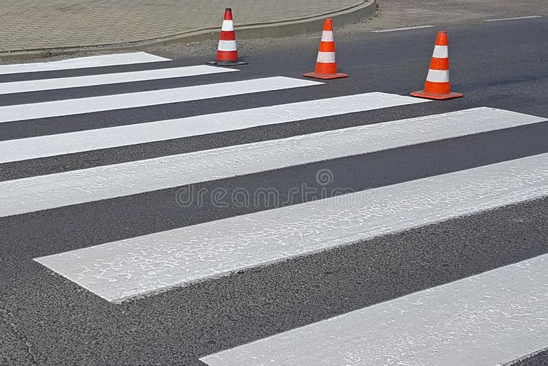 The cross-decorated pedestrian crossing with the still not dried out red. Restriction of traffic by road signs. Update road pedest. Rian markings. Luminescent royalty free stock photos