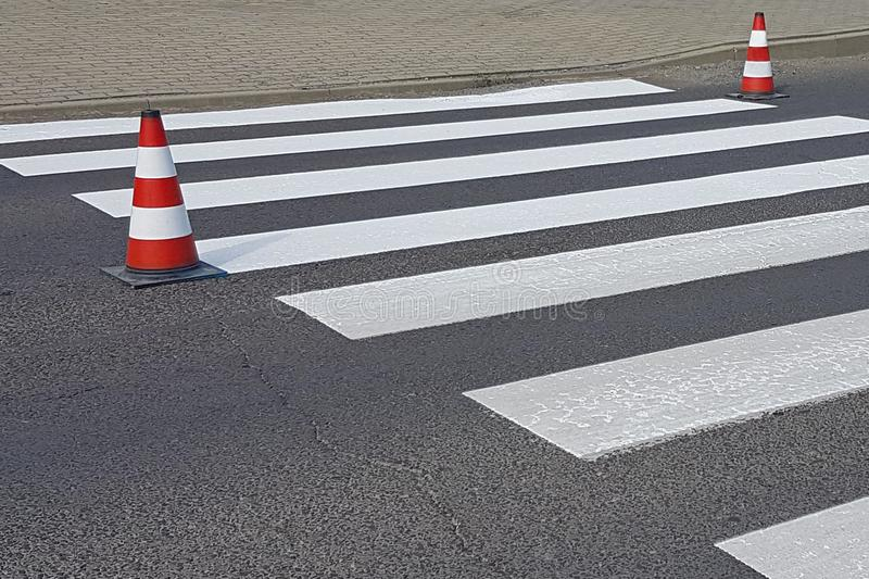 The cross-decorated pedestrian crossing with the still not dried out red. Restriction of traffic by road signs. Update road pedest. Rian markings. Luminescent royalty free stock images