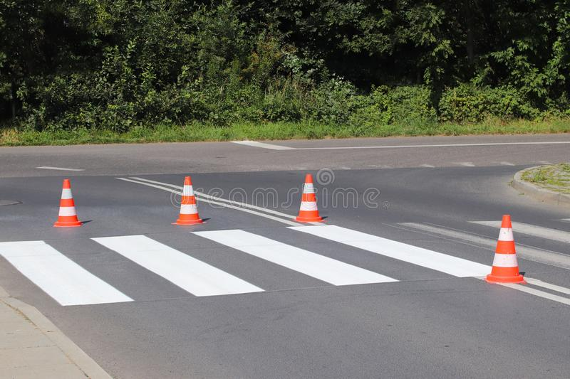 The cross-decorated pedestrian crossing with the still not dried out red. Restriction of traffic by road signs. Update road pedest. Rian markings. Luminescent stock photos