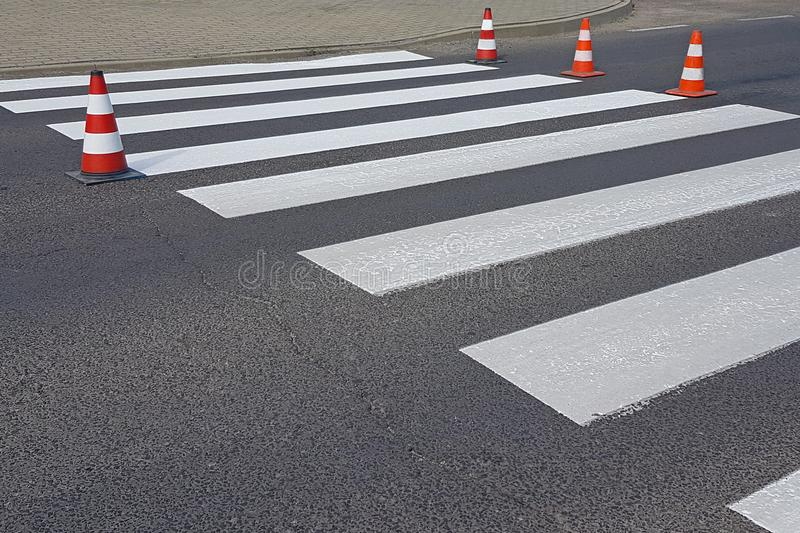 The cross-decorated pedestrian crossing with the still not dried out red. Restriction of traffic by road signs. Update road pedest. Rian markings. Luminescent royalty free stock photography