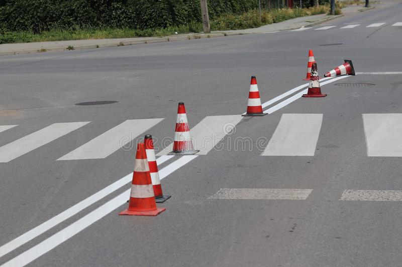 The cross-decorated pedestrian crossing with the still not dried out red. Restriction of traffic by road signs. Update road pedest. Rian markings. Luminescent royalty free stock photo