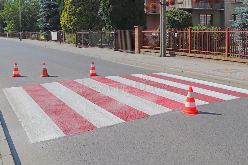 The cross-decorated pedestrian crossing with the still not dried out red. Restriction of traffic by road signs. Update road pedest. Rian markings. Luminescent royalty free stock image