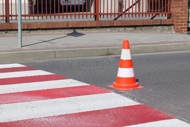 The cross-decorated pedestrian crossing with the still not dried out red. Restriction of traffic by road signs. Update road pedest stock images