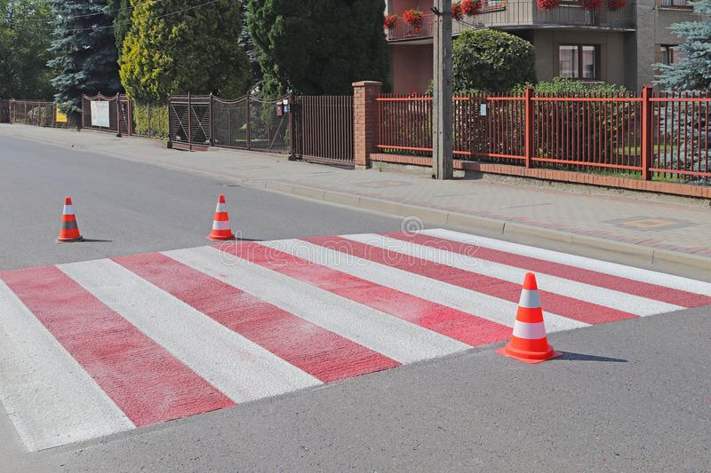 The cross-decorated pedestrian crossing with the still not dried out red. Restriction of traffic by road signs. Update road pedest royalty free stock image