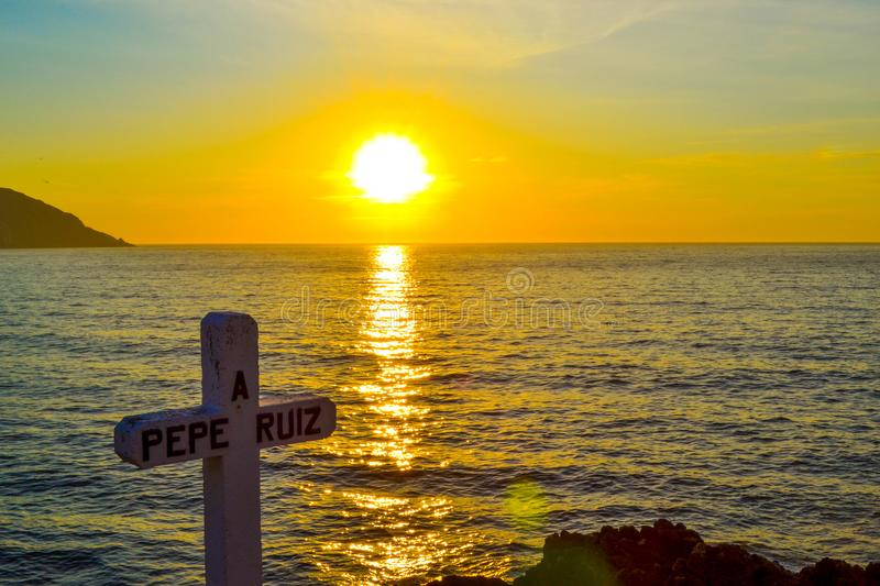 A cross dedicated to the death of sailor Pepe Ruiz in Punta Robaleira, Cabo Home, Spain. Beautiful sunset over the sea and rocks royalty free stock images