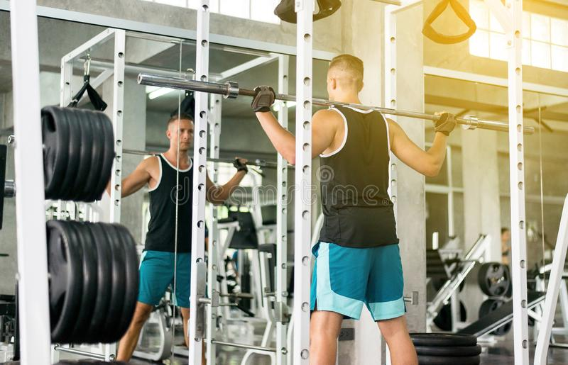 Cross fit body and muscular lifting bar bell weights in the gym,Sport man doing exercises training,Back view royalty free stock photo