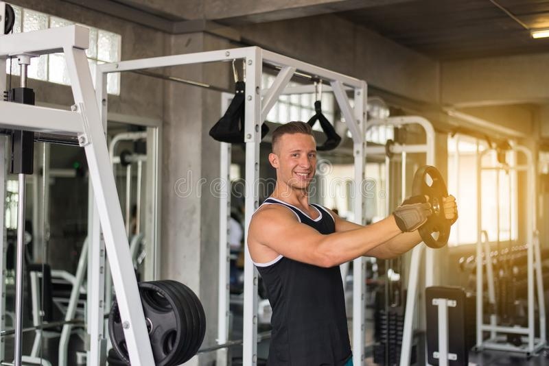 Cross fit body and muscular lifting weight bar in the gym,Sport handsome male doing exercises training. Cross fit body and muscular lifting weight bar in the gym stock photos