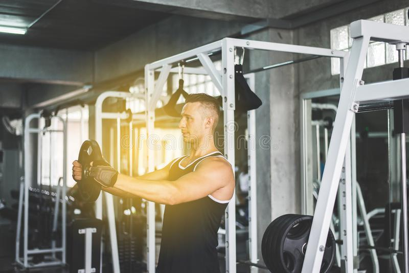 Cross fit body and muscular lifting weight bar in the gym,Sport man doing exercises training stock photo