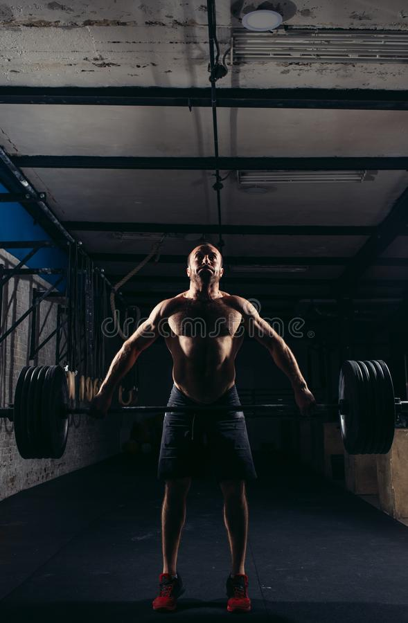Crossfit fitness gym heavy weight lifting bar by strong man workout stock photo