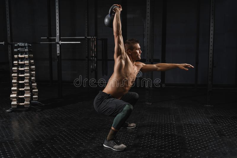 Kettlebells swing exercise man workout at gym. Crossfit training. Cross fit training in a gym. Kettlebells swing exercise man workout at gym royalty free stock photos