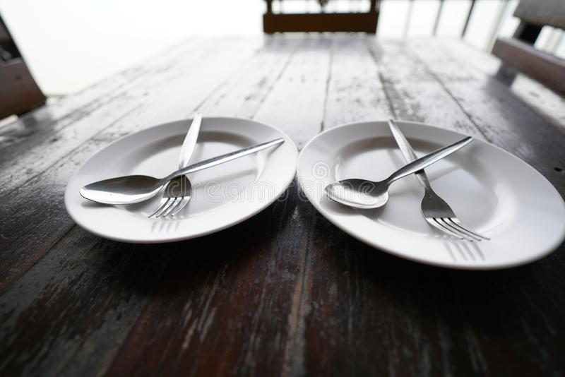 cross fork and spoon on the white dish on wood table stock image