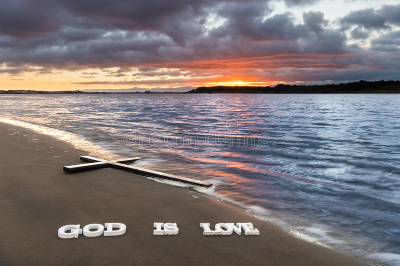 Cross God is Love. Cross on a river beach with the words `God is Love` below it royalty free stock photos