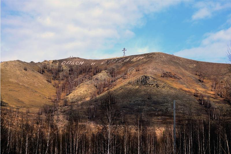 """Cross and inscription on the mountain """"bless and save"""". Karabash, Russia. Landscape, forest, manufacturers, orange royalty free stock photos"""