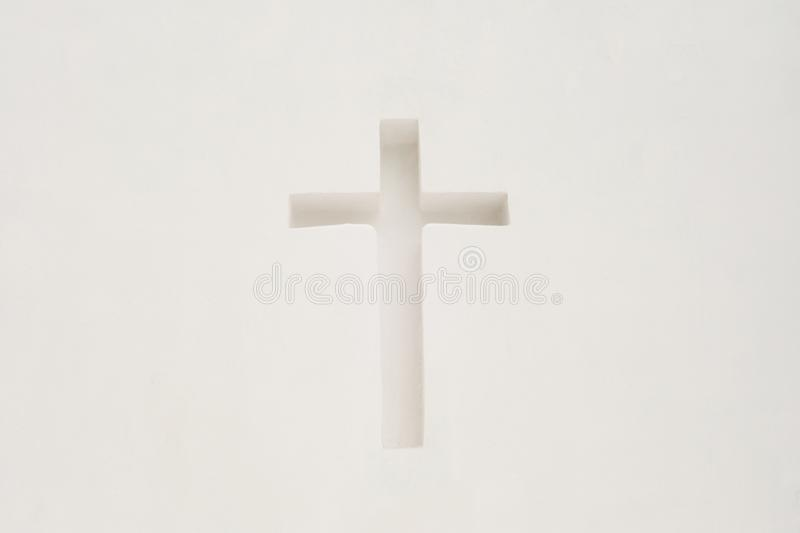 Cross in a white wall. Religious symbol royalty free stock photography