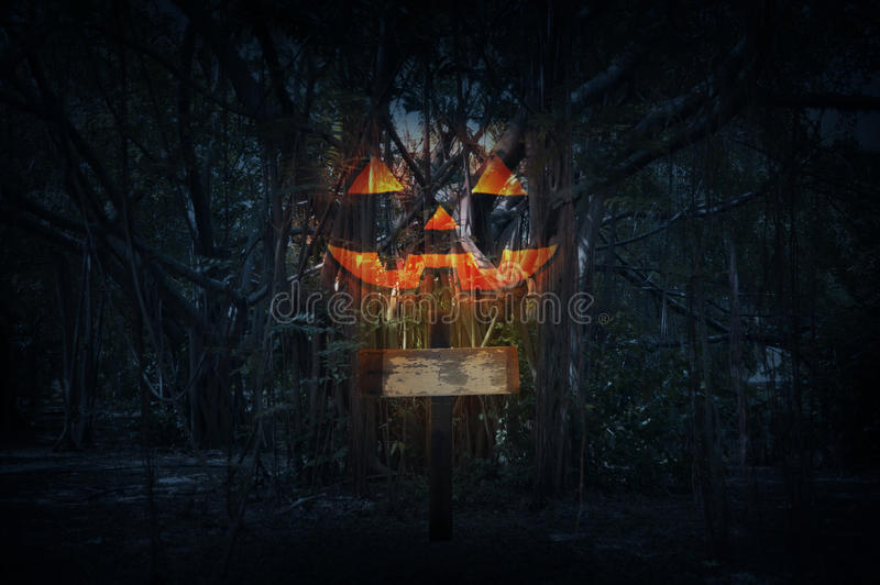 Cross with Jack O Lantern pumpkin over spooky forest at night ti royalty free stock images