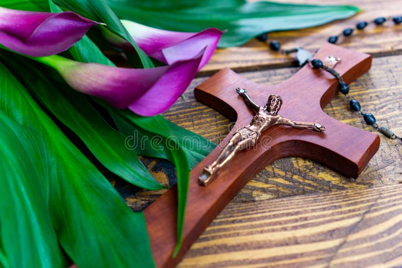 Cross with jesus christ on a wooden background with a purple calla - religious easter lent concept stock photography