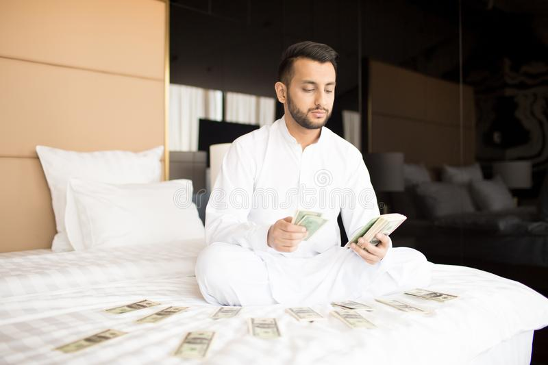 Rich man. Cross-legged businessman in white clothes counting his money or salary while sitting on bed stock photos