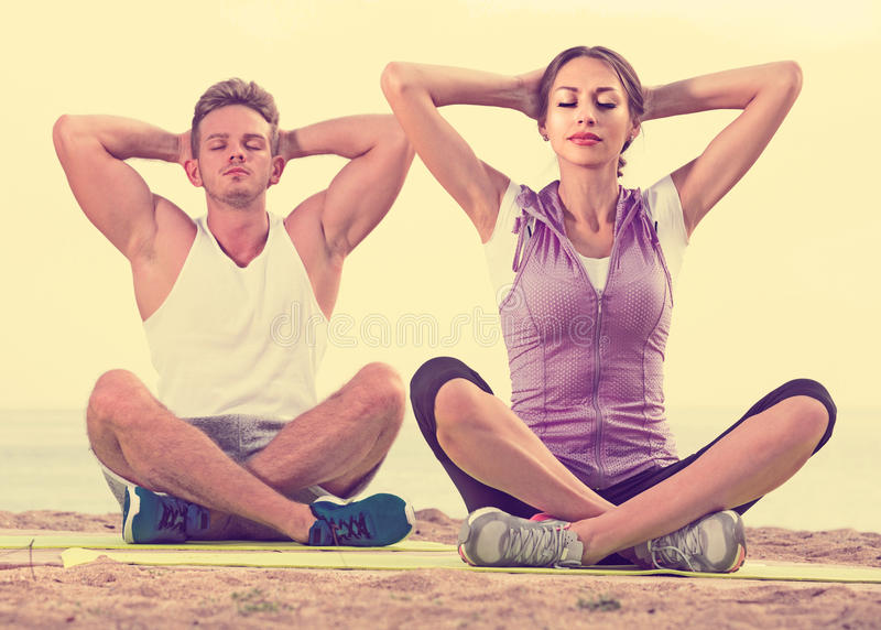 Download Cross-legged Couple Practice Yoga On Beach In Morning Stock Photo - Image: 83701443