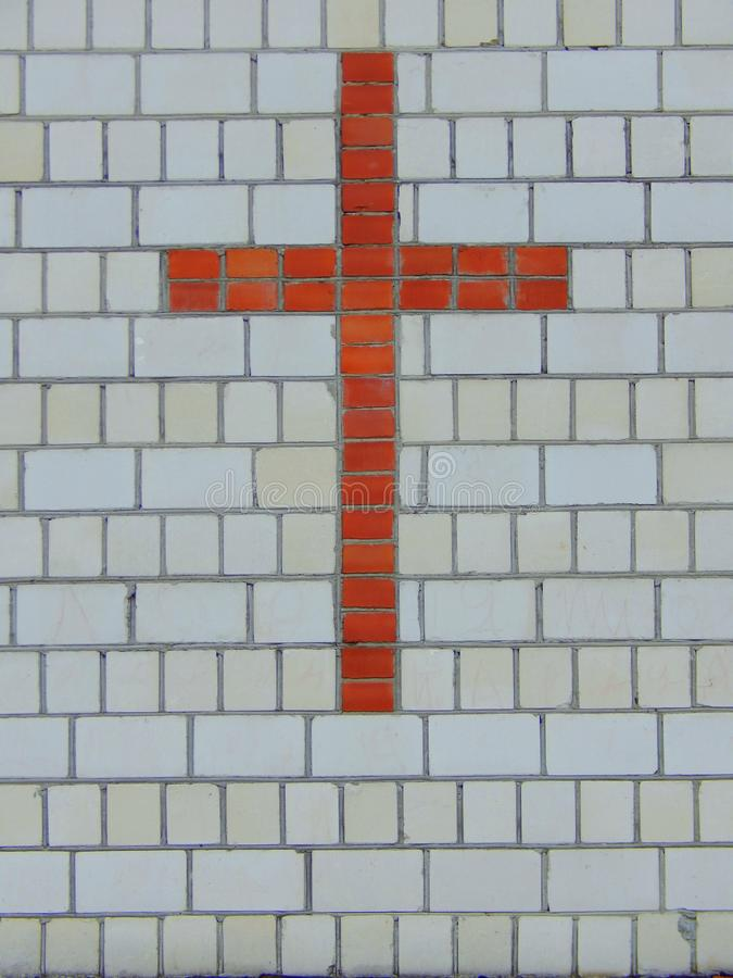 Cross of red brick on a wall of white brick royalty free stock photography
