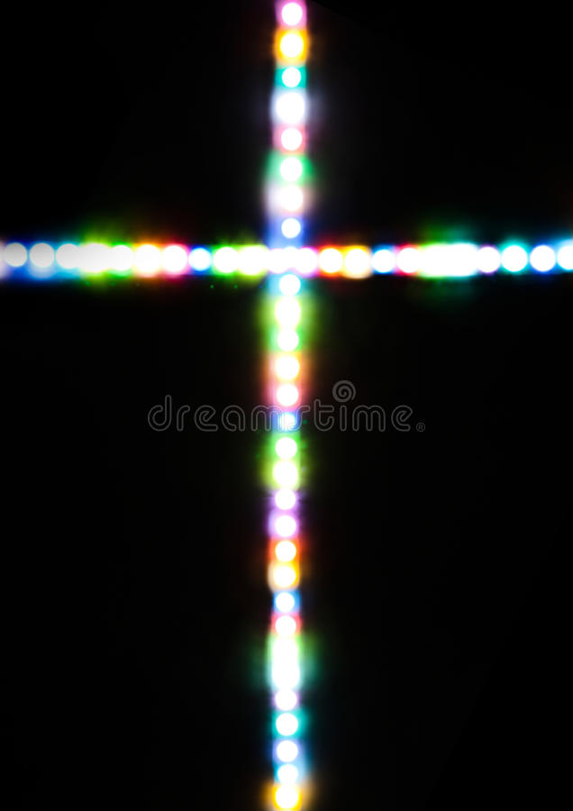 Cross made with several light colors. With black background stock photography