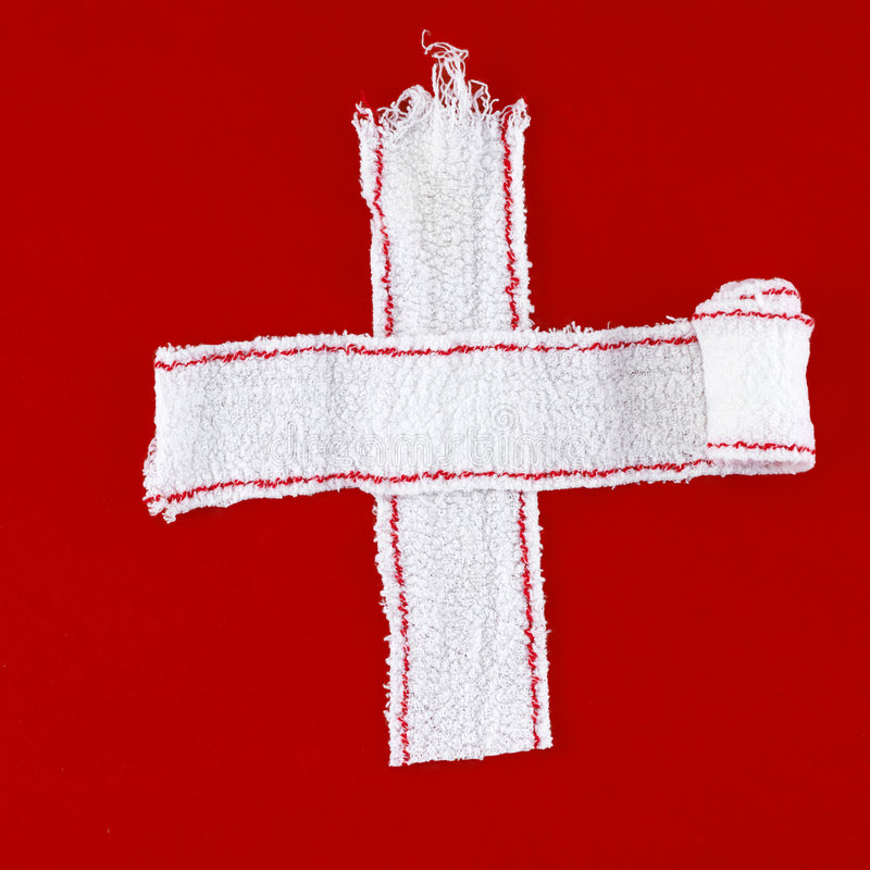 Cross made of white bandages (red background). Cross made of white bandages on a red chalk background stock image