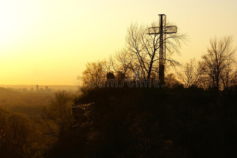 A cross monument overlooking a misty city landscape at sunset stock image