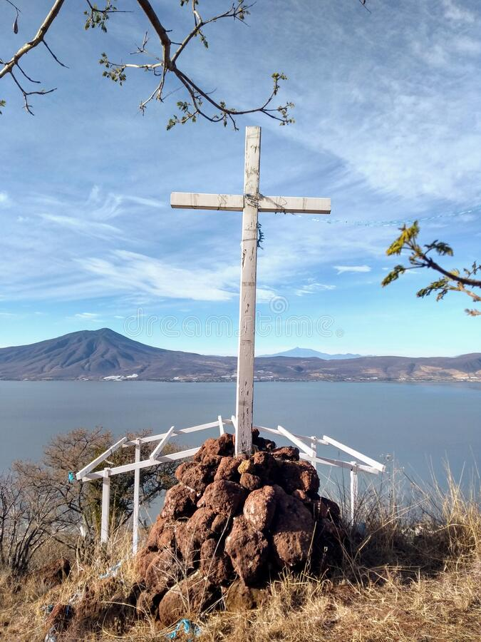 cross on mountain by lake royalty free stock image