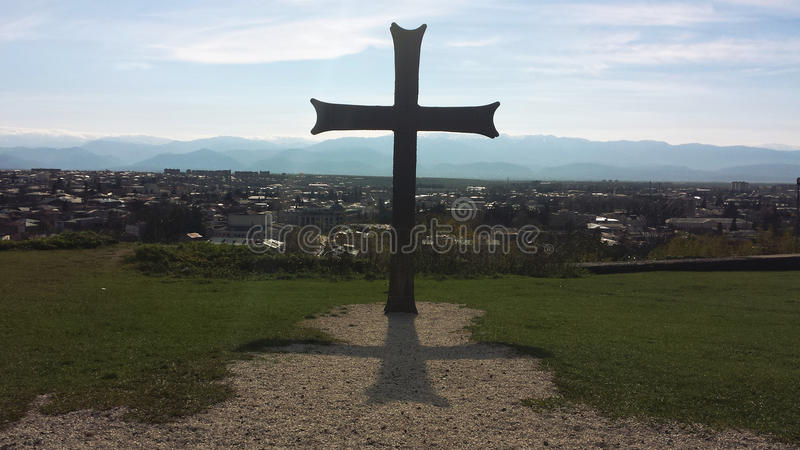 Cross over city in Kaukasus. Cross in mountains over city in Kaukasus against blue sky royalty free stock image