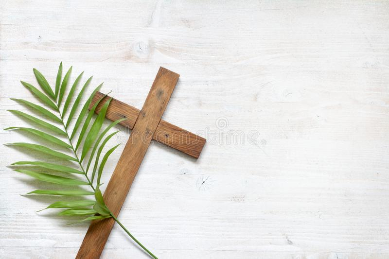 Cross and palm on wooden white background easter sign symbol concept. Closeup stock images