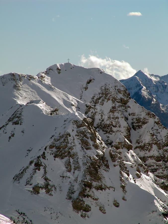 Cross on peak. Mountain cross on top of the hill stock image