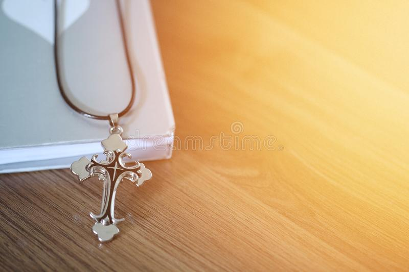Cross pendant over the book on wooden floor with light flare and copy space stock photos