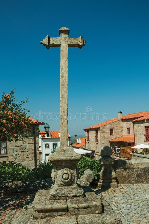 Cross shape pillory made of stone in courtyard and old houses stock photos