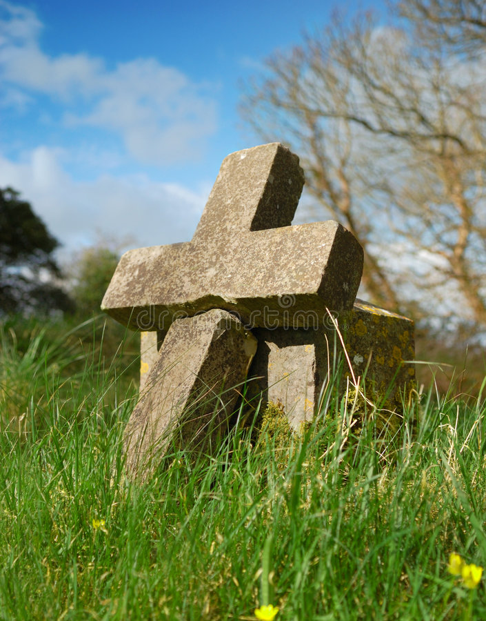 Cross shaped grave stone. Old granite headstone marking ancient grave stock photos