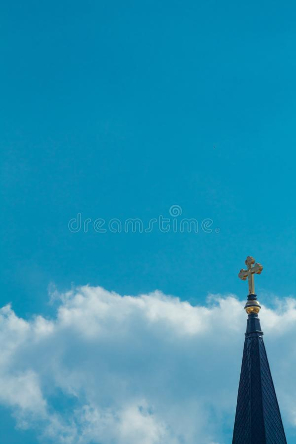 Cross in the Sky. A awesome gold cross with a cloudy blue sky stock images