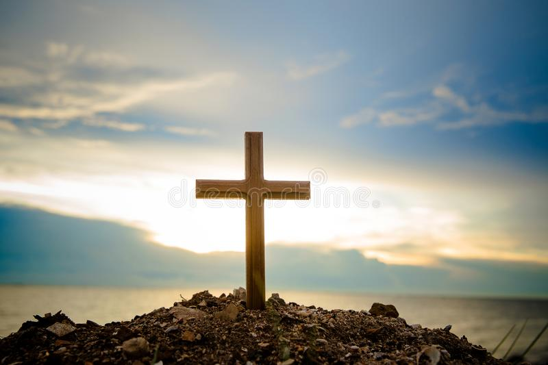 The cross standing on meadow sunset and flare background. Cross on a hill as the morning sun comes up for the day. stock image