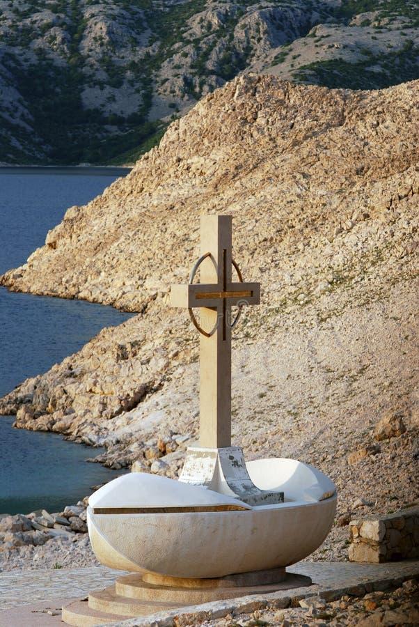 Cross statue in Novalja on island Pag in Dalmatia,Croatia. Vertical photo of marble cross statue near the sea in Novalja on island Pag in Dalmatia,Croatia royalty free stock photos