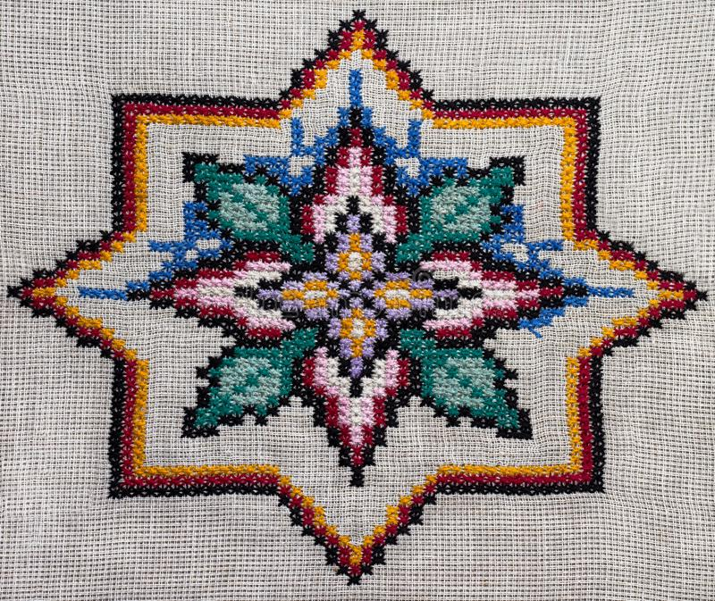 Cross-stitch handmade embroidery. The round colorful pattern royalty free stock image