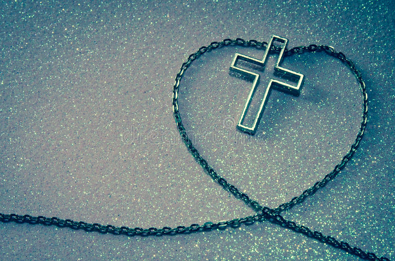 Cross symbol in chain love shape. Silver cross symbol in love shape image royalty free stock images