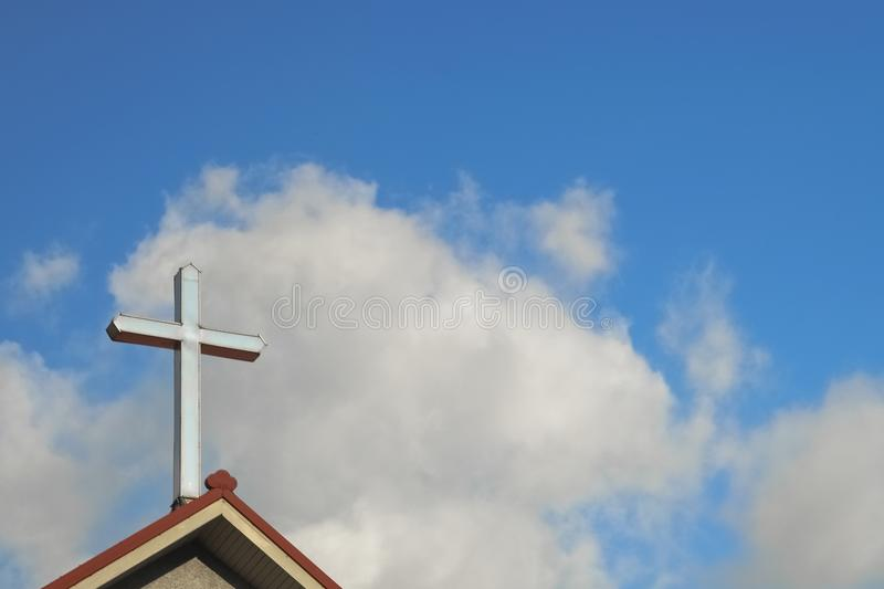Cross on top of church, with sky and clouds behind. Good for use as background.  stock images